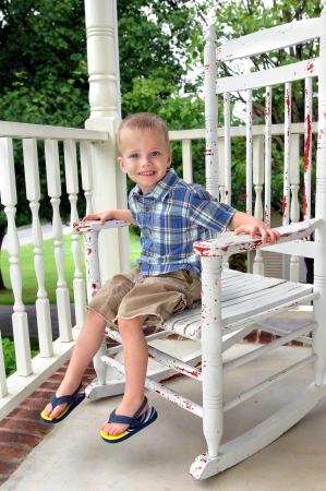 Small boy grins as he sits on a weathered rocking chair on the front porch of his home   He is wearing flip flops, shorts and short sleeved shirt  Stock Photo