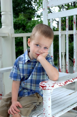 elbow chair: Small boy sits in a white wooden rocking chair on his front porch   He is leaning on his elbow and waits patiently for his family