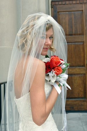 strapless: Bride peeks between the folds of her veil as she waits outside the church doors   She is holding her bouquet of red and orange roses up to her face