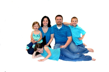 Close family of five dressed in jeans, aqua and all barefoot, sit in all white room   All are smiling and happy  Stock Photo