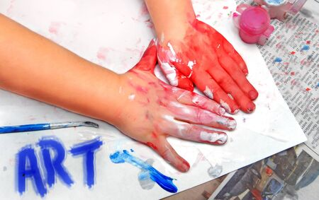 smeared: Little hands have created a masterpiece   Paint smeared hands and paper   Paintbrush in corner