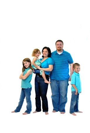 Family of five stand in jeans, aqua shirts and barefoot in a room of all white   All are smiling and happy