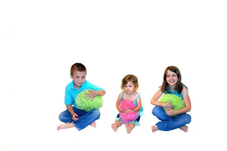 Two sisters and a brother play with colorful, suffed and fuzzy balls in hot pink and green   They are all dressed in jeans, barefoot and sitting in an all white room