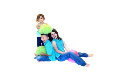 Three kids dressed in jeans and aqua colors play with stuffed, fuzzy balls in hot colors   All are barefoot and holding a colorful ball