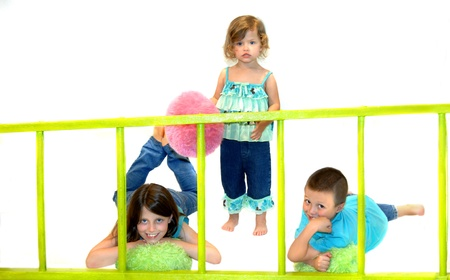Two sisters and a brother play with fun fuzzy balls and a brilliant green ladder   All are barefoot and holding fuzzy stuffed balls