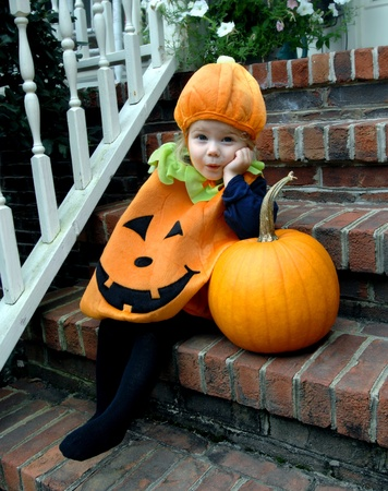 Cute little girl, wearing a pumpkin costume, leans impatiently on a pumpkin   She is waiting for Halloween to arrive  Stock Photo - 15024128