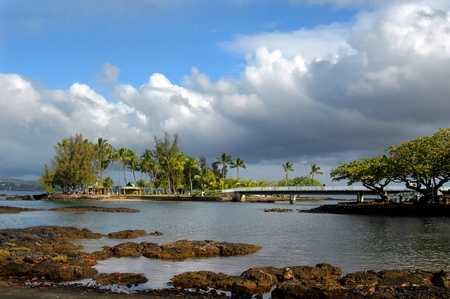 Storm clouds clear and the blue pops through over Coconut Island on the Big Island.  A man gazes over the railing of the connecting bridge. Banque d'images