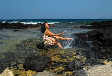 Older Hawaiian woman wades into the shallows and is sitting on a black lava rock kicking and splashing. photo