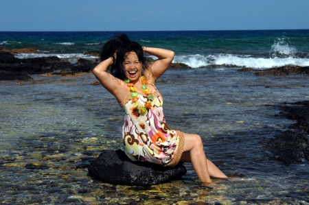 Hawaiian woman sits on a rock in shallow water and celebrates by throwing her hair up and posing.  Anaehoomalu Bay on the Kohala Coast of the Big Island of Hawaii. photo