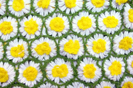 Hand knitted daisies are linked by bright green yarn.  Background image.
