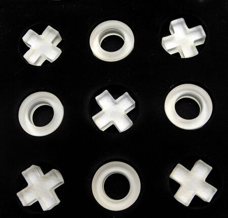 x marks the spot: Tic tac toe game pieces fill round holes in black felt box.  It could also represent the hugs and kisses symbols. Stock Photo