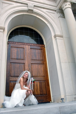 pulled over: Bride kneels in front of the chapel door holding her bouquet.  She is looking up and has her gown pulled up over her knees.  She is deep in thought.