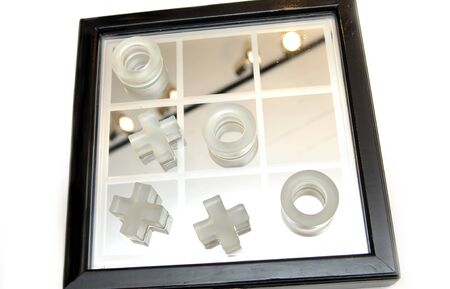 x marks the spot: Wooden box has mounted mirror and glass tic tac toe game   Game sits on white background   The O has the game won  Stock Photo