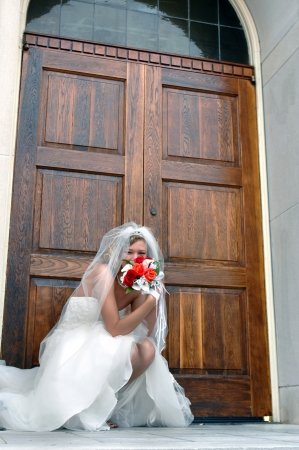 strapless dress: Bride kneels besides the chapel door, anticipating the doors opening for the ceremony   She is teasingly hiding her face behind he bouquet of red and orange roses  Stock Photo