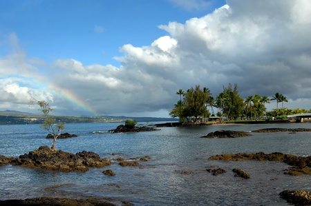 arching: Peque�a isla en la isla grande de Hawaii es Coconut Island Un puente arqueado de metal que se conecta a la reciente tormenta de lluvia continental deja un arco iris sobre el �rea y la bah�a de Hilo Foto de archivo