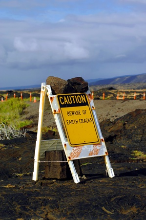 stating: Sign is secured with lava rocks   White folding sign with yellow caution sign attached stating  Beware of earch cracks    Volcanoes National Park on Big Island of Hawaii