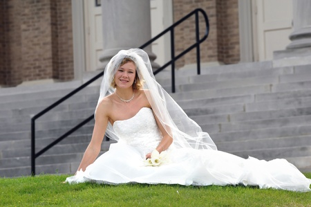 strapless: Beautiful bride leans confidently on the grass as she waits for wedding ceremony to start   Blond curly hair and a happy smile