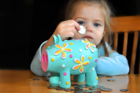 nickle: Sad child puts a nickle into a brightly decorated piggy bank   Background is dark as are her chances in life