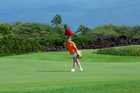Woman stands besides hole marked by a red flag on a golf course on the Big Island of Hawaii   Mauna Loa rises in the background behind golf course  photo