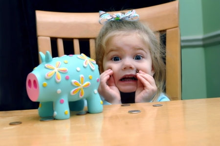 Little girl looks upset that she has to save all her pennies   She is holding two against her cheek   Brightly colored aqua piggy bank sits besides her at their kitchen table  Stock Photo