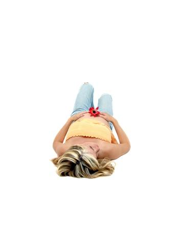 sprawled: El embarazo puede ser totalmente absorbente, y esta mujer joven pone en silencio en un cuarto blanco y contempla el futuro Ella est� sosteniendo una flor rosa �nico y tiene su est�mago ampliaci�n mostrando