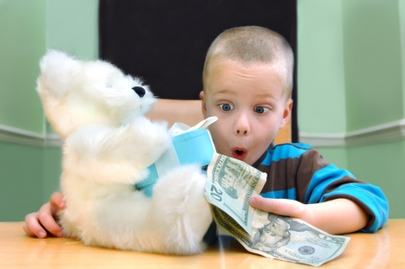 bugging: Little boy holds his birthday present, a stuffed bear with attached blue box   The box is open and money is spilling out onto the kitchen table   The boy has his eyes and mouth open in surprise