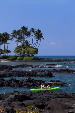 Mother and daughter kayak the rocky shores of Anaehoomalu Bay on the Big Island of Hawaii    Stock Photo - 15024475