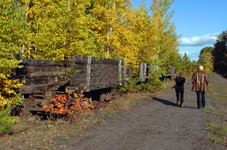 backroad: Couple explore a backroad above Quincy Copper Mine and discover old wooden, ore cars rotting amoung the fall foliage of upper penninsula, Michigan