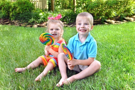Brother and sister sit on the grass with a huge rainbow colored lollipop   They have sugar and color on their faces from lollipops  photo