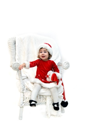 Little girl awaits Santa Claus   She is dressed in Christmas costume and holding a Santa doll  photo