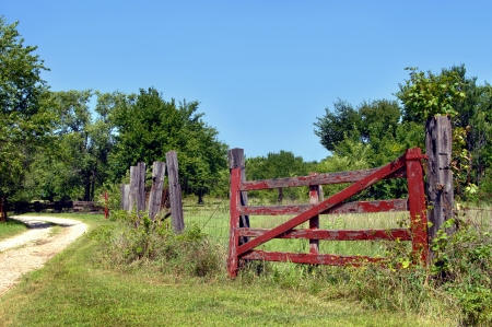 Rustic red, wooden gate is overgrown with weeds and leaning   Curving dirt lane leads to Kansas backroad farm  photo