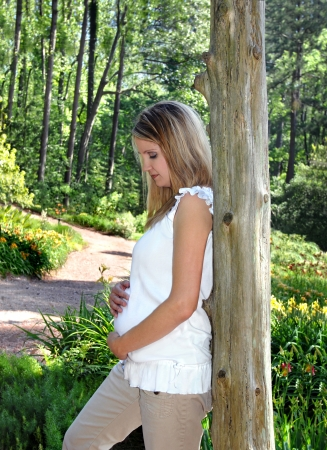 Mother gently holds her unborn baby in the shady Birmingham Botanical Gardens   She is leaning against a rustic pole and looking downward  Stock Photo - 15044745