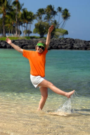frolicking: Adult female celebrates retirement by kicking and splashing on the beach on the Big Island of Hawaii   She is wearing a sunvisor and sunglasses   Could also be a metaphor for  blancing act
