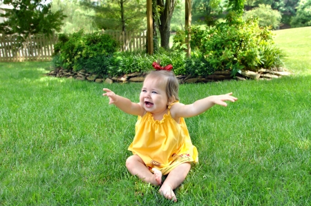 flapping: This baby will fly early   She has her hands out and flapping her wings   She is sitting barefoot on the grass in a bright yellow dress   Her mouth is open and her two bottom teeth are showing  Stock Photo