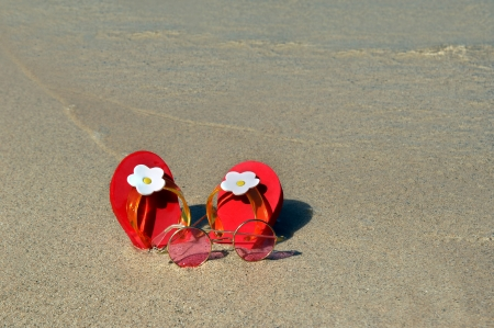 Tiny red flip flops, decorated with white daisies, sit in the sand at waters edge   Gentle waves lap at flip flops and rosy tinted sunglasses just the right size for a little girl  photo