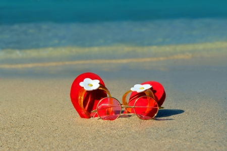 Tiny red flip flops, decorated with white daisies, sit in the sand at waters edge   Flip flops are half buried in the golden sand   Metaphor  rosy tinted glasses   rest alongside   Just the right size for a girly little girl  photo