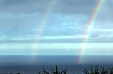 Double rainbow appears after a brief shower on the Big Island of Hawaii   The end of the rainbow shows up as it ends on the surface of the ocean on the Hamakua Coast