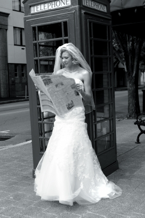 absorbed: Bride keeps updated on current events even on her wedding day   She is leaning against a vintage phone booth on a corner in downtown   Newspaper is in her hands and she is absorbed in the news  Stock Photo