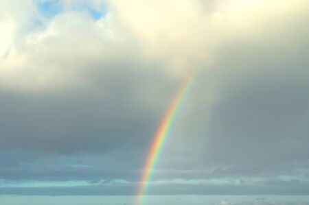 Rainbow appears out of a grey mass of clouds with rain still showering down behind arc   Blue sky breaks through at top of photograph  photo
