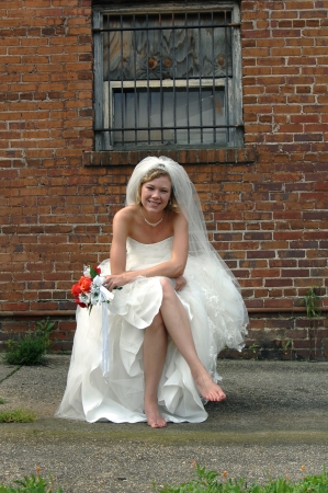 Bride sits alone in an alley with aging brick building behind her   Bars and wood cover window over her head   She is smiling and holding her bouquet of red and orange roses