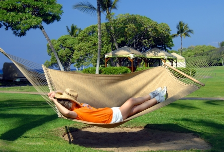 Older woman lays in a hammock slung between two palm trees on a resort on the Kohala Coast of the Big Island of Hawaii   Her straw hat lays across her face and she is swinging to the rhythm of the trade winds