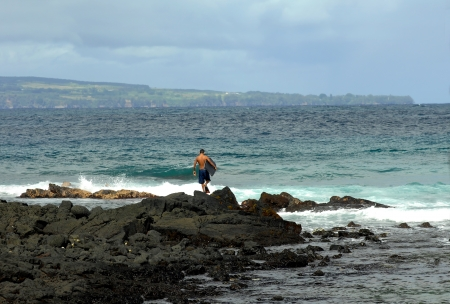 Young man carrying a boogie board and wearing flippers walks out across the rocks to enter the ocean for a day of fun boogie boarding  photo