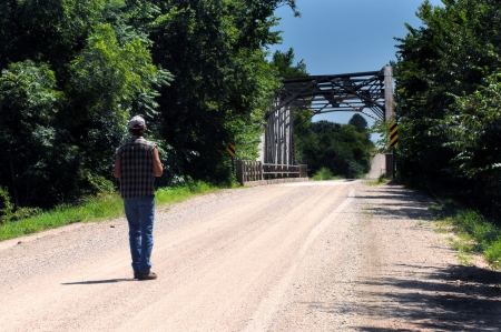 Man walks a lonely gravel road   Bridge is in front of him and a long stretch of empty road ahead   He is wearing a cut off shirt, cap and jeans  photo