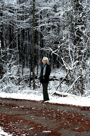 bundling: Elderly woman gets her winter exercise by bundling up and walking down a quiet backroad   She is wearing a black leather jacket, print scarf and mittens