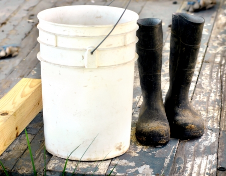 Muddy work boots set besides a five gallon bucket on a wooden porch   Porch boards are cracked and peeling   Work gloves lay in background   Boots represent a  work ethic   Banque d'images