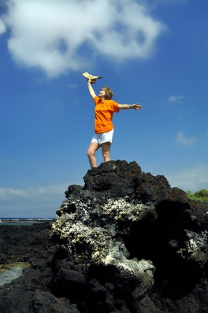 exhilarated: Woman celebrates her retirement standing on top of her mountain   She has climbed to the top of a black lava rock on the Big Island of Hawaii   Her hat is thrown skyward