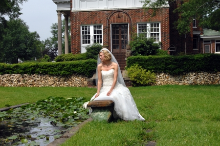 Bride sits surrounded by beautiful home, gardens and lush green grass   Her gown is strapless and she is holding calillies  photo