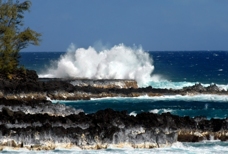 windward: Windward side of the Big Island of Hawaii has lava rock outcroppings and wild waves   A large wave hits stratus colored rocks of black, brown, white and grey