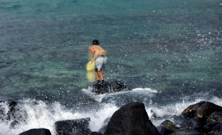crouches: Fisherman on the rocks of the Big Island of Hawaii crouches ready to throw his fishing net.  He is wearing a hat, shorts and black water shoes. Stock Photo
