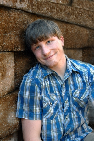 Young male teenager grins happily as he leans his head against a stone wall.  His blue eyes match the blue in his plaid snap up shirt. photo